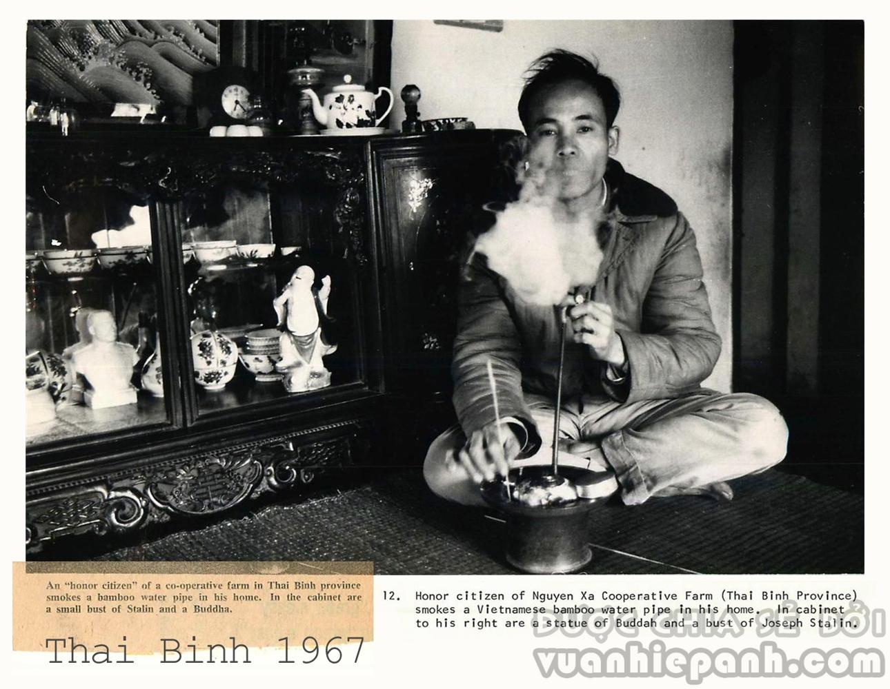 Thái Bình 1967- Xã viên tiên tiến hợp tác xã nông nghiệp xã Nguyên Xá (Vũ Thư, Thái Bình) hút thuốc lào tại nhà. Trong tủ là một tượng Phật và một tượng bán thân của Joseph Stalin. Ảnh: Lee Jonathan Lockwood/Black Star